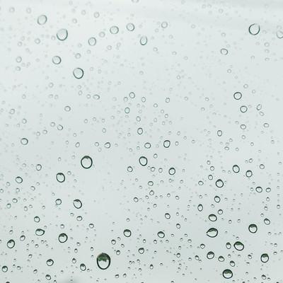 窓ガラスと雨の水滴の写真