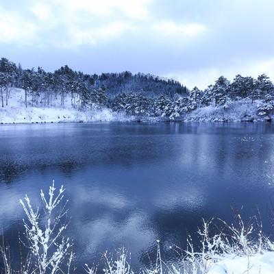 山間の沼と雪景色の写真