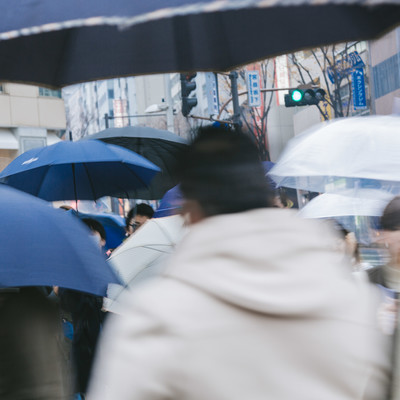傘をさす歩行者の写真