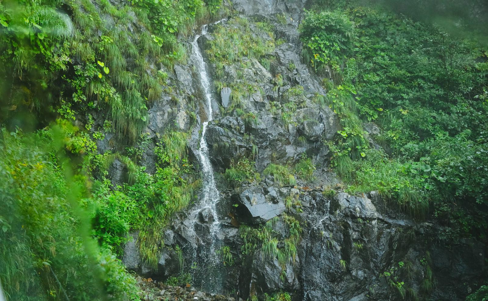 「山の斜面から流れる大量の雨水」の写真