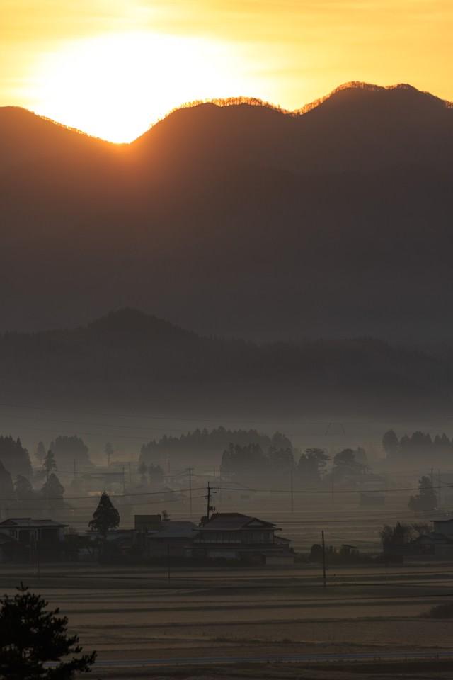 夜明け、霧に包まれた田舎の写真