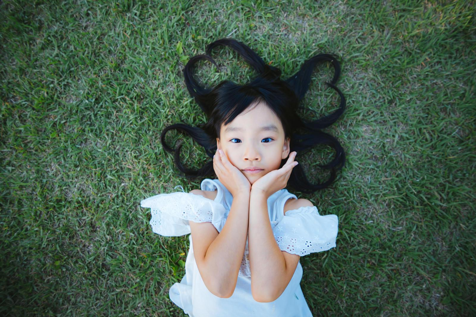 「芝生で寝転ぶ女の子(髪の毛ハート)」の写真[モデル:あんじゅ]