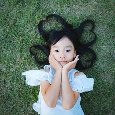 芝生で寝転ぶ女の子(髪の毛ハート)の写真
