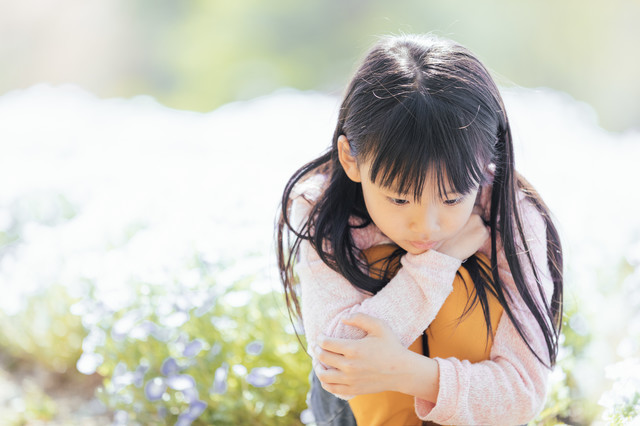 お花畑でうつむく女の子の写真