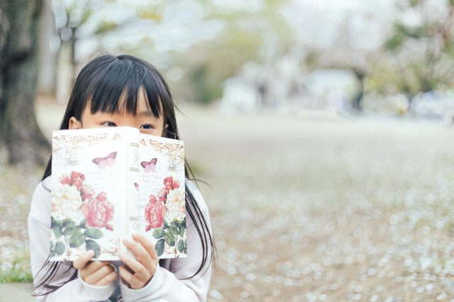 聖書を読みながら考え事をするクリスチャンの少女の写真