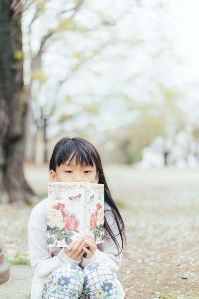 公園で洋書を広げる女の子の写真