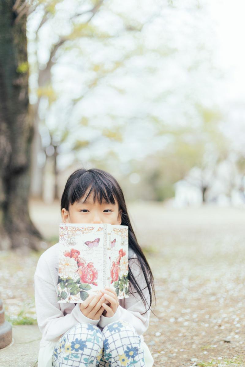 「公園で洋書を広げる女の子」の写真[モデル:あんじゅ]