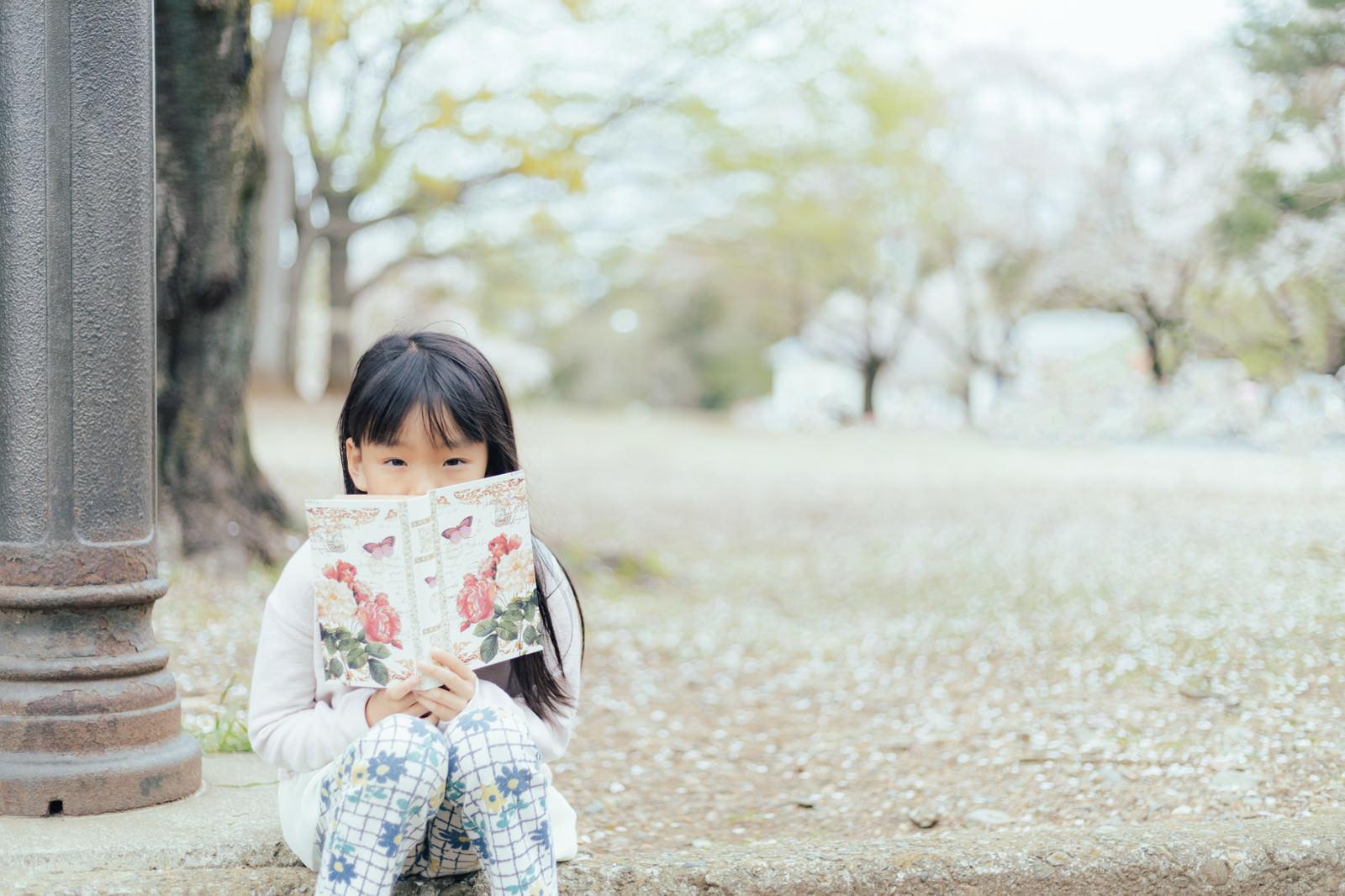 「公園で洋書を読む女の子」の写真[モデル:あんじゅ]