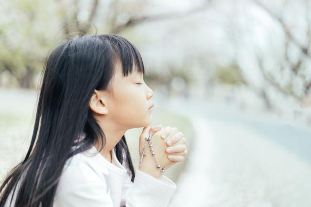 ロザリアを握り祈るクリスチャンの子供の写真
