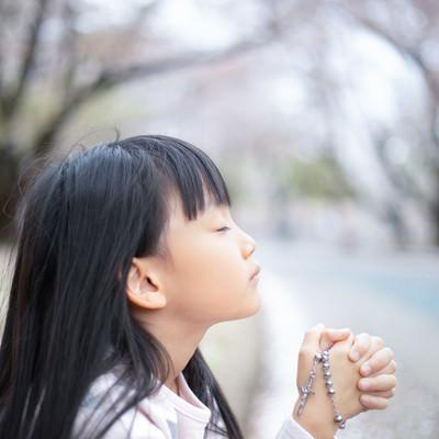 神様に祈りを捧げる女の子の写真