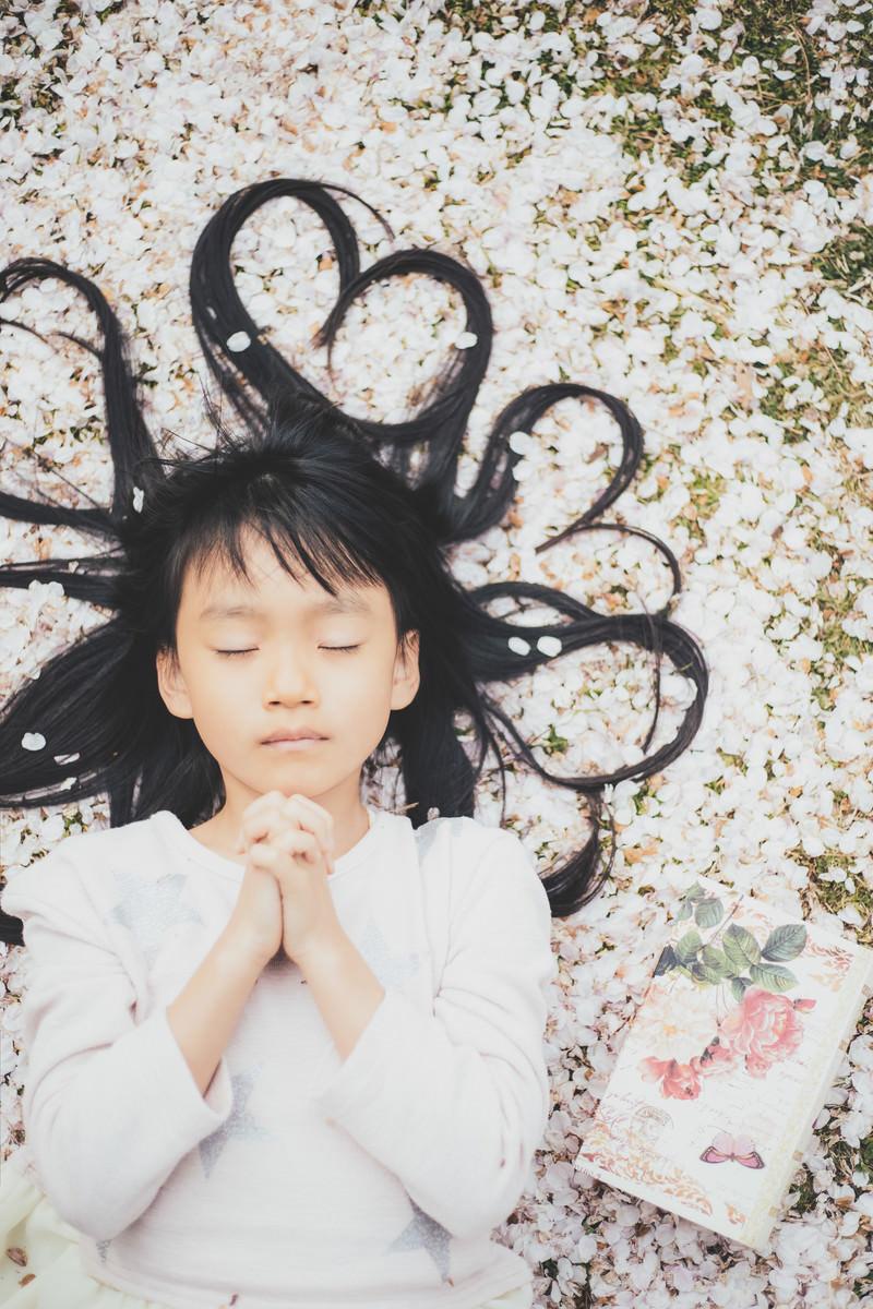 「桜の花びらに横たわり祈る女の子」の写真[モデル:あんじゅ]
