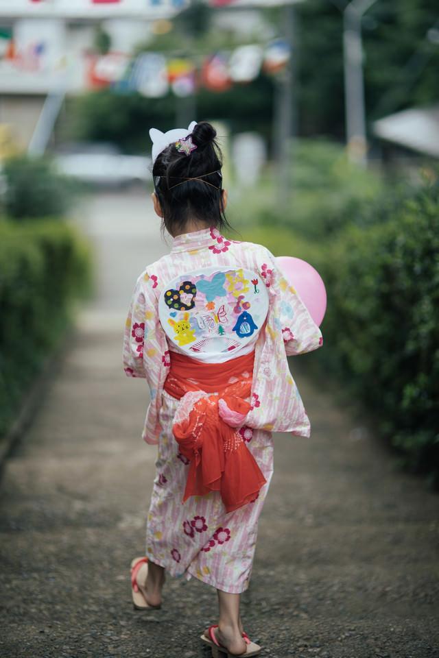 お祭り帰りの浴衣少女の後ろ姿の写真