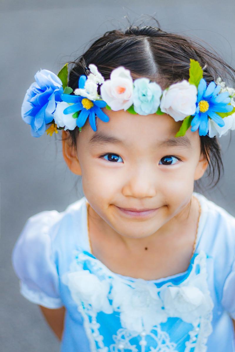 「花飾りを着けたにっこり笑顔の女の子」の写真[モデル:あんじゅ]