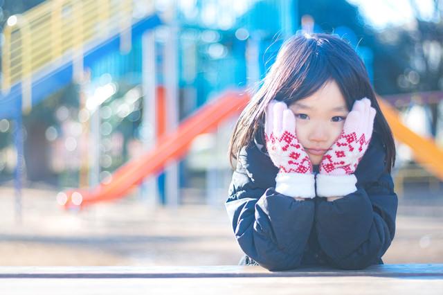 寒くてほっぺをおさえる女の子の写真