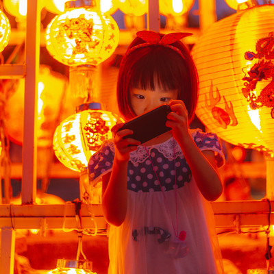 お祭りの提灯とスマホに夢中の女の子の写真