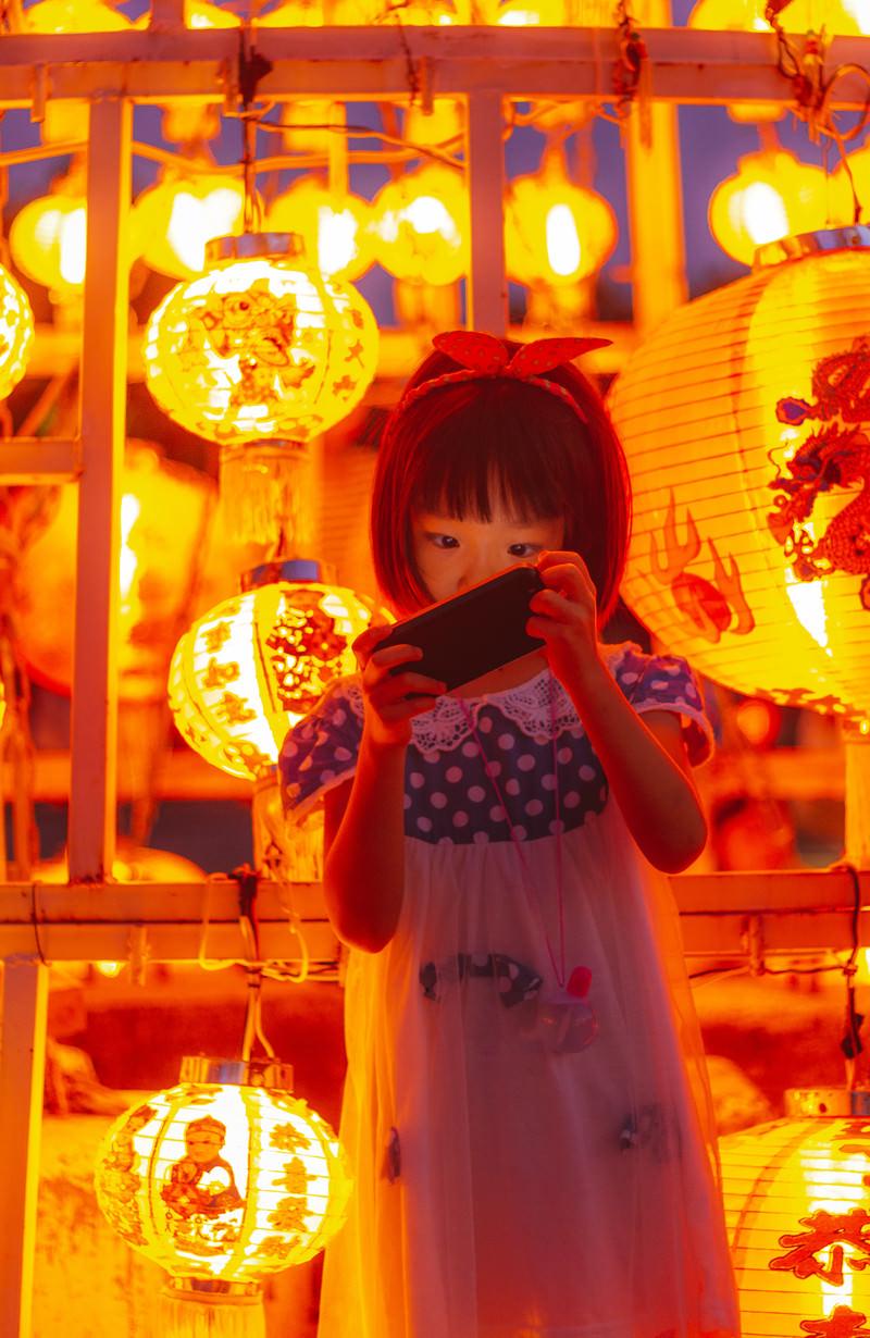「お祭りの提灯とスマホに夢中の女の子」の写真[モデル:あんじゅ]