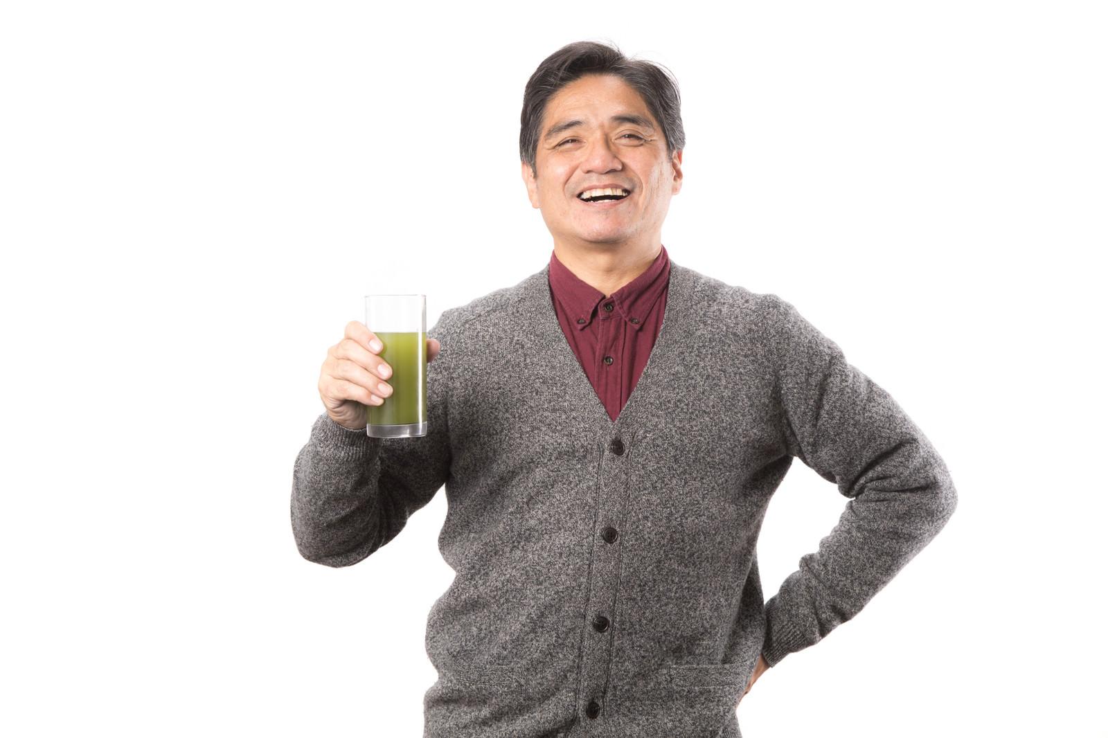 「野菜不足を補う青汁を笑顔で紹介する中年男性」の写真[モデル:よたか]
