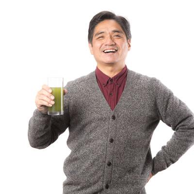 「野菜不足を補う青汁を笑顔で紹介する中年男性」の写真素材