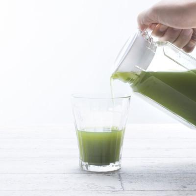 「ポットからタンブラーに青汁を注ぐ」の写真素材