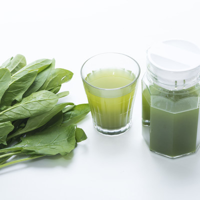 「葉物野菜とポットに入った青汁、グラス」の写真素材