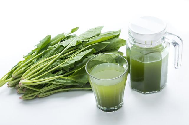 葉物野菜と青汁のグラスの写真