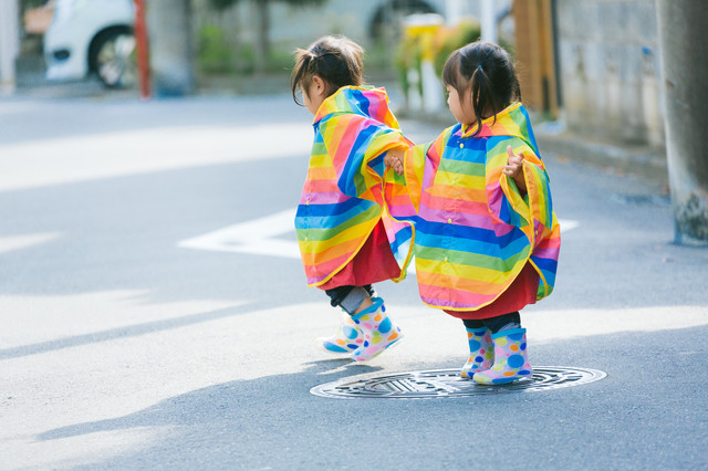 カラフル合羽で仲良く散歩する双子の写真