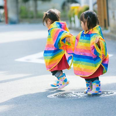 「カラフル合羽で仲良く散歩する双子」の写真素材