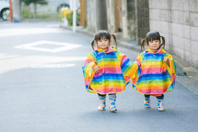 仲良く手をつないで散歩する双子の姉妹(2歳)の写真