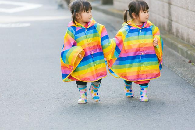 手をつないで仲良く歩く風な双子の写真