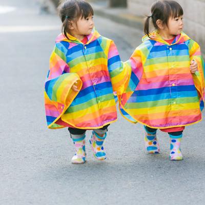 「手をつないで仲良く歩く風な双子」の写真素材