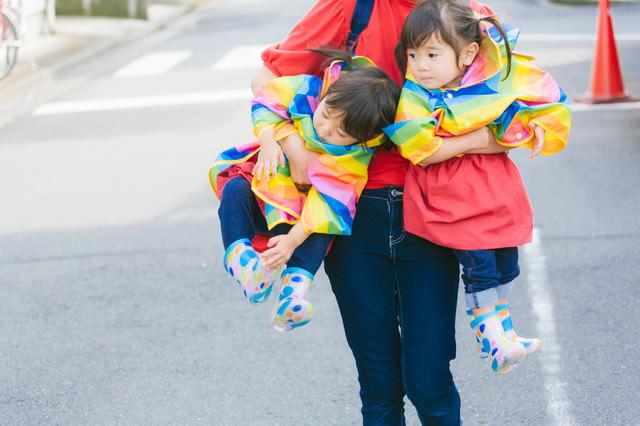 ママに抱きかかえられる双子の姉妹の写真