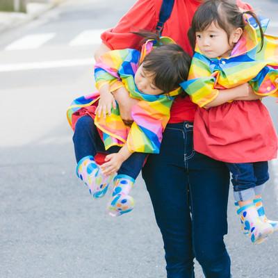 「ママに抱きかかえられる双子の姉妹」の写真素材