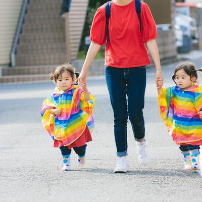 「ママと手をつなぐ双子の女児」の写真素材