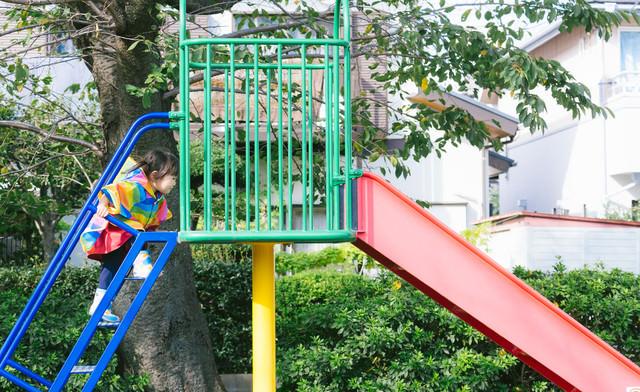 滑り台の階段を駆け上がる子どもの写真