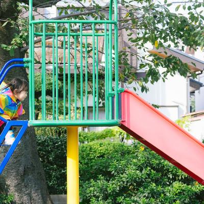 「滑り台の階段を駆け上がる子ども」の写真素材