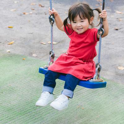 「ブランコデビューの小さい女の子」の写真素材
