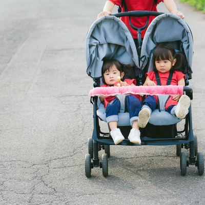 「二人乗りベビーカーに乗った双子の姉妹」の写真素材