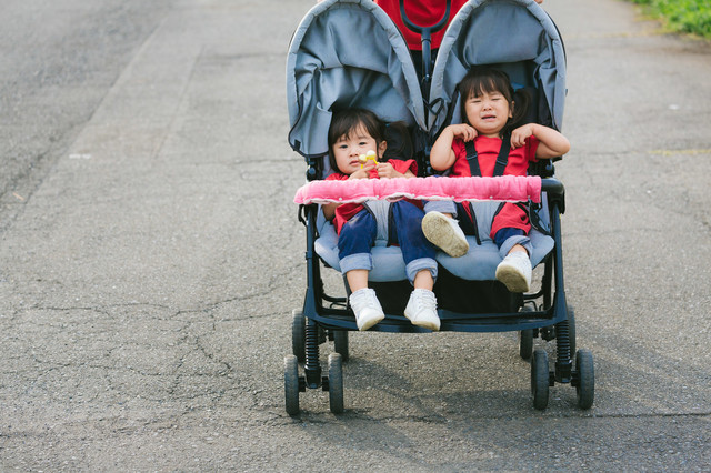 ベビーカーで愚図る双子の女の子の写真