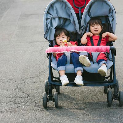 「ベビーカーで愚図る双子の女の子」の写真素材