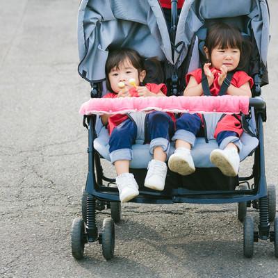 「泣いても仲良しの双子の女児(ベビーカー)」の写真素材