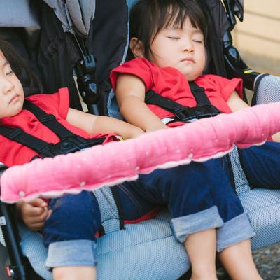 「ベビーカーの上で寝てしまった双子女児」の写真素材