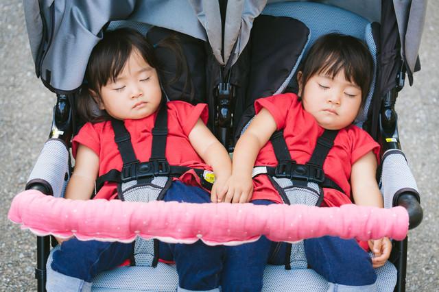 二人乗りベビーカーで爆睡中の双子姉妹の写真