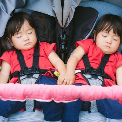 「二人乗りベビーカーで爆睡中の双子姉妹」の写真素材