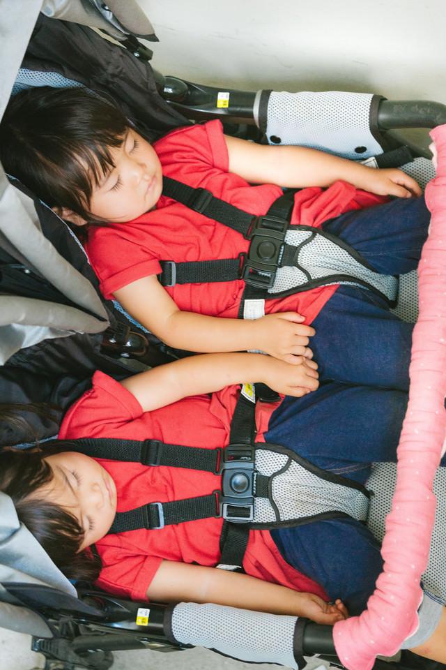 ベビーカーの上でぐっすり眠る双子の女児の写真