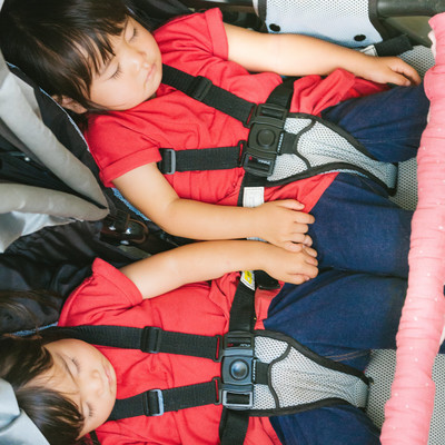 「ベビーカーの上でぐっすり眠る双子の女児」の写真素材