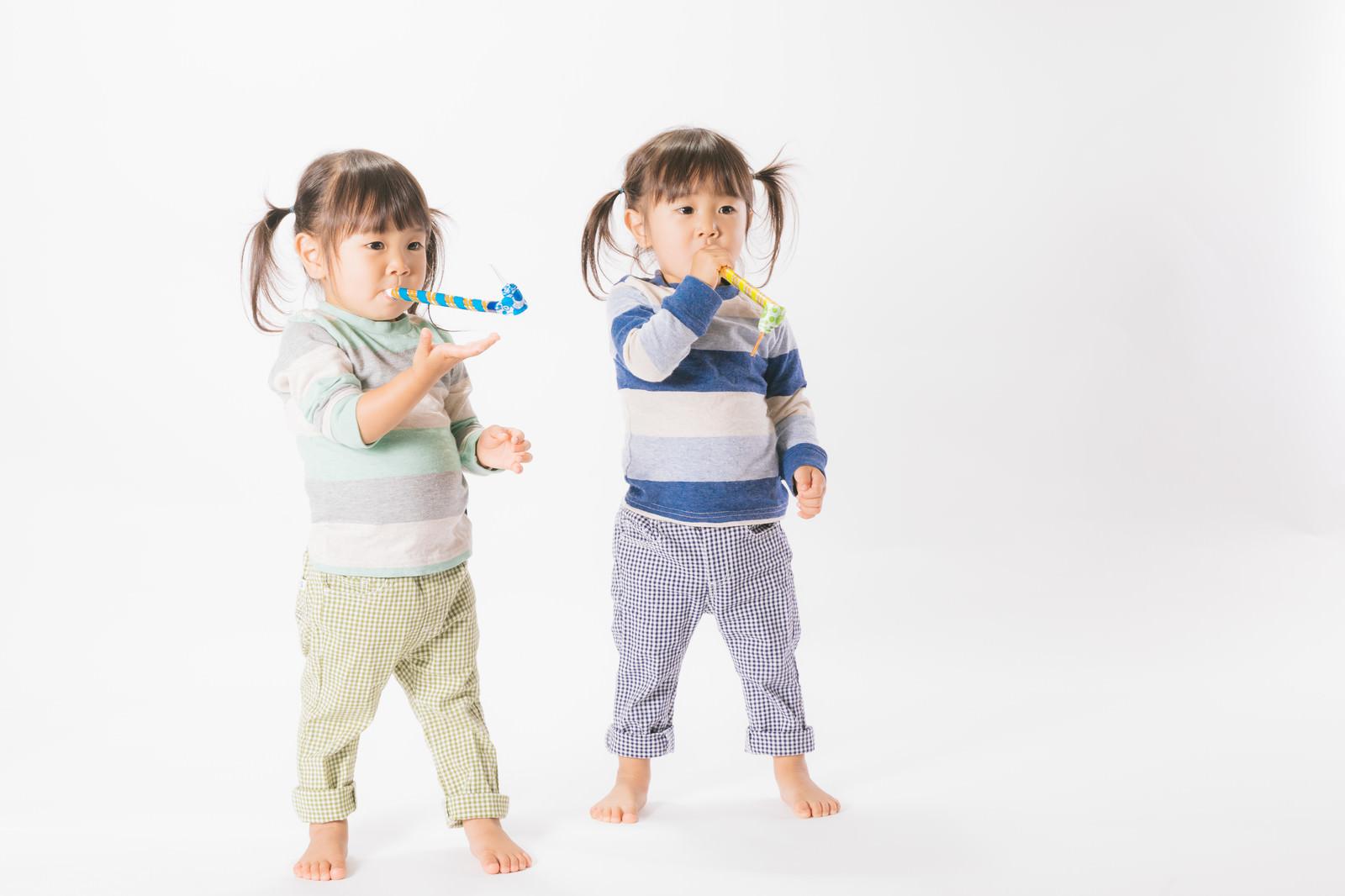 「与えられたピロピロプーに夢中な子供(双子)」の写真[モデル:あおみどり]