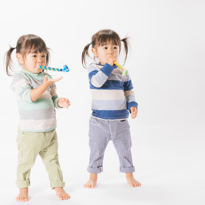 「与えられたピロピロプーに夢中な子供(双子)」の写真素材