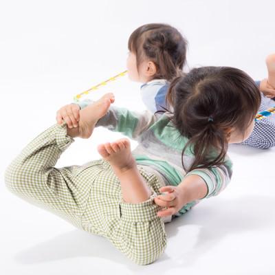 「ピロピロプーを咥えながらはしゃぐ息の合った双子姉妹」の写真素材