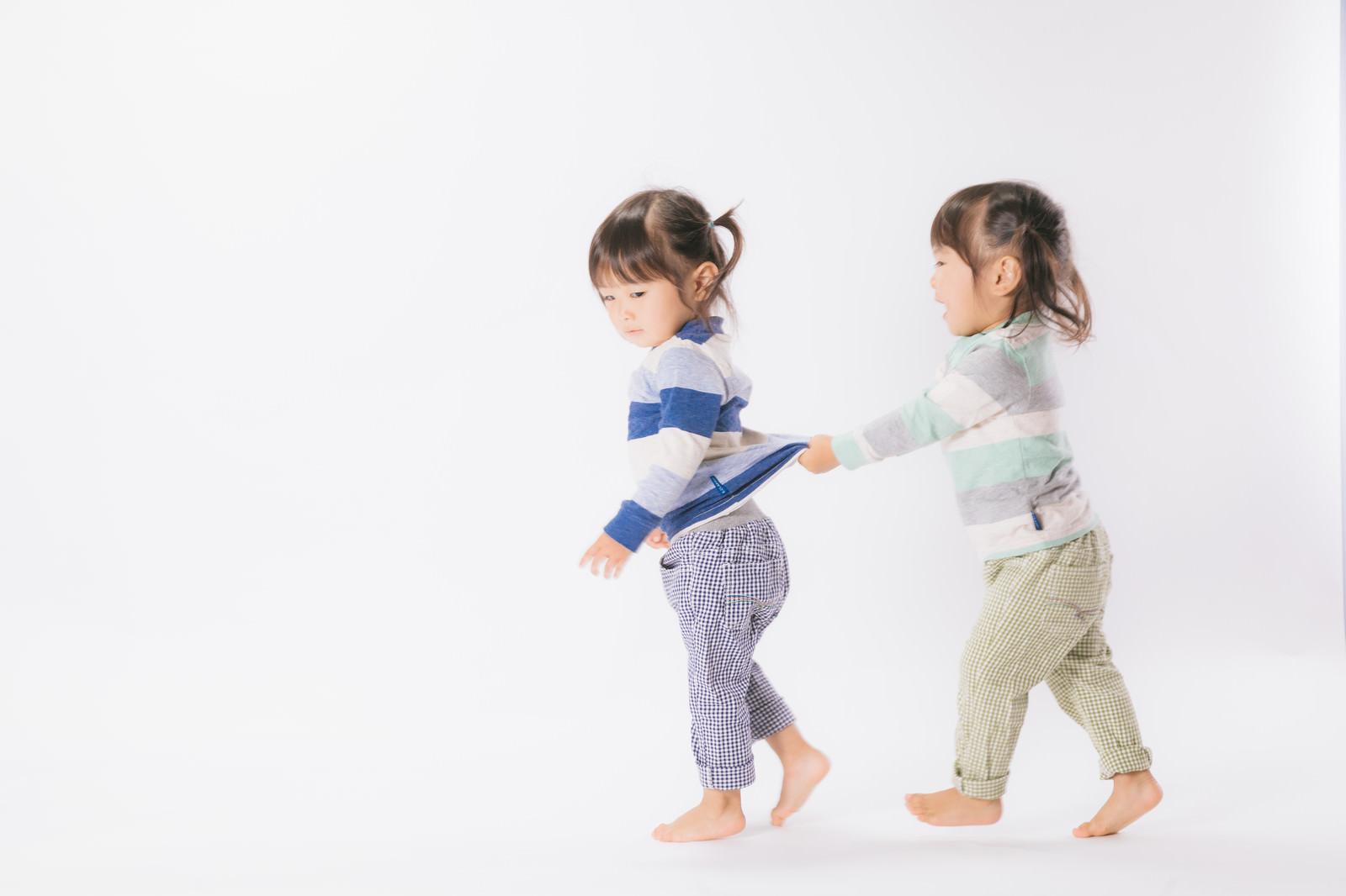 「怒る姉と服をひっぱる妹(双子)」の写真[モデル:あおみどり]