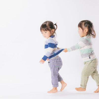 「怒る姉と服をひっぱる妹(双子)」の写真素材